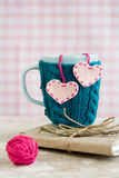 Błękitna filiżanka w różowym pulowerze z odczuwanymi sercami z piłką przędza Zdjęcie Royalty Free