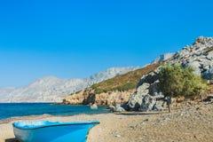 Błękitna fishermans łódź i wiecznozieloni tamarisks na plaży blisko Emborios Greckiej wioski na Kalymnos wyspie Alexi lub Alexis Zdjęcie Stock