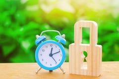 Błękitna kłódka i budzik Trwałej rzeczy ochrony sprawdzony w czasie ochrona i stabilność Oszczędzanie czas Pojęcie chwilowy obrazy stock