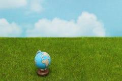 Błękitna kula ziemska na zielonej trawie nad niebieskiego nieba tłem zdjęcie stock