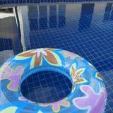 Błękitna nadmuchiwana round tubka z kwiatu projektem na pływackim basenie Zdjęcie Stock