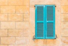 Błękitna nadokienna żaluzja i kamienna ściana śródziemnomorski dom zdjęcie stock