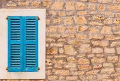 Błękitna nadokienna żaluzja i kamienna ściana śródziemnomorski dom obraz royalty free
