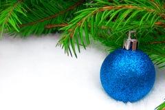 Błękitna nowy rok piłka z zielonym jedlinowym drzewem na śnieżnym tle fotografia stock
