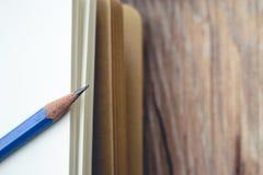 Błękitna ołówkowa bela pusta książka na drewnianym Obrazy Stock