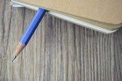 Błękitna ołówkowa bela pusta książka na drewnianym Zdjęcie Stock