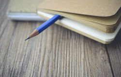 Błękitna ołówkowa bela pusta książka na drewnianym w rocznika brzmieniu Obrazy Royalty Free