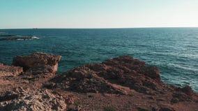 Błękitna ocean woda i brąz skaliste falezy z słońcem na horyzoncie Koral plaża w Cypr Widok z lotu ptaka błękitny ocean wody kara zdjęcie wideo