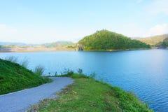 Błękitna rzeka, zielony wzgórze i droga blisko strony tama, Obrazy Stock