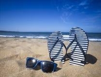 Błękitna sandała trzepnięcia klapa i okulary przeciwsłoneczni na piasku wyrzucać na brzeg z błękitnym morza i nieba tłem w wakacj Obrazy Stock