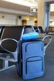 Błękitna walizka przy lotniskowym lobby Zdjęcia Royalty Free