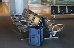 Błękitna walizka przy lotniskowym lobby Zdjęcie Royalty Free