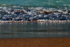 Błękitne foamy fale przychodzi brązowić piaskowatą plażę obrazy stock