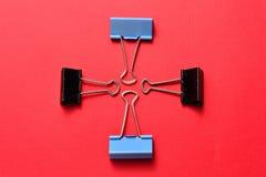 Błękitne i czarne segregator klamerki na czerwonym tle Obraz Stock