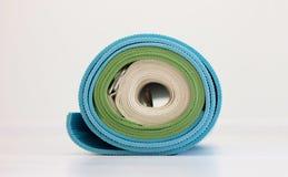 Błękitne i zielone joga maty i biel patka przekręcająca wpólnie obrazy stock