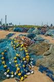 Błękitne sieci rybackie z żółtymi pływaczkami rozprzestrzeniają na ziemi przy schronieniem Elmina, Ghana, afryka zachodnia Zdjęcia Stock