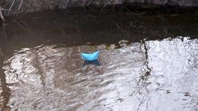 Błękitnego papieru łódź barwiony papier unosi się wzdłuż brzeg rzeki zbiory