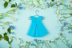 Błękitnego papieru origami suknia na wieszaku otaczającym z błękitnymi i białymi małymi kwiatami na światło mennicy tle Zdjęcie Royalty Free