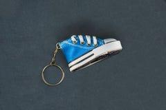 Błękitnego sneeaker kluczowy łańcuch odizolowywający na czarnej tkaninie Obraz Stock