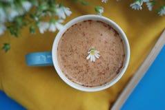 Błękitnej filiżanki kawy mleka Latte napoju Cynamonowych kijów tła Drewnianej Żółtej pieluchy rumianku kwiatu Buquet Nieociosany  Obrazy Stock