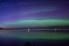 Błękitnej zieleni i purpur zorzy borealis odbijali nad jeziorem Obraz Stock