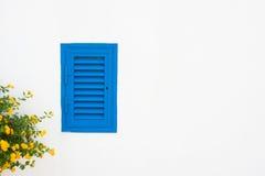 Błękitni żaluzja koloru żółtego i okno kwiaty na biel ścianie obrazy royalty free