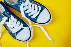Błękitni żeńscy lub męscy sneakers na kolorze żółtym tapetują tło zdjęcie stock