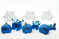 Błękitni bożych narodzeń baubles z płatkami śniegu na śniegu i prezenty Fotografia Royalty Free