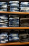 Błękitni drelichowi cajgi w stojaku w sklepie odzieżowym obrazy royalty free