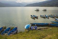Błękitni drewniani catamarans na wodzie i łodzie wioślarskie łodzie na jeziorze przeciw tłu zielone góry faceci pod zdjęcie royalty free