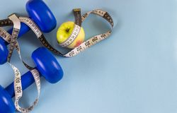 Błękitni dumbbells, pomiarowa taśma i jabłko na błękitnym tle, fotografia stock