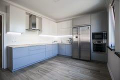 Błękitni i biali gabinety w nowożytnym kuchennym wnętrzu fotografia stock