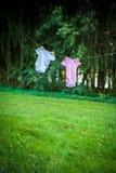 Błękitni i Różowi rompers wiesza w lesie Fotografia Stock
