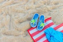 Błękitni kapcie z kolorową rozgwiazdą i ręcznikiem na piasku na plaży obraz royalty free