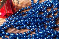 Błękitni koraliki z czerwonym boże narodzenie dzwonem na starym drewnianym tle Obrazy Stock
