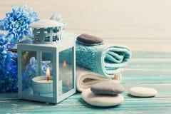 Błękitni kwiaty, otoczaki i blask świecy, obrazy stock