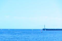 Błękitni morze, niebieskie niebo i latarnia morska, zdjęcia stock