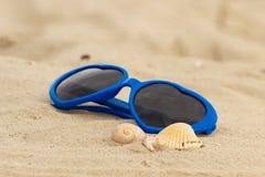 Błękitni okulary przeciwsłoneczni kształtowali serce z skorupami na piasku Obrazy Stock