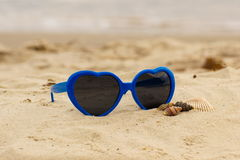 Błękitni okulary przeciwsłoneczni kształtowali serce z skorupami na piasku Zdjęcie Stock