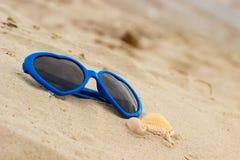 Błękitni okulary przeciwsłoneczni kształtowali serce z skorupami na piasku Zdjęcie Royalty Free