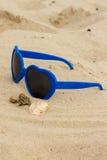 Błękitni okulary przeciwsłoneczni kształtowali serce z skorupami na piasku obrazy royalty free