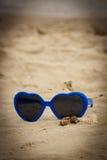 Błękitni okulary przeciwsłoneczni kształtowali serce z skorupami na piasku fotografia royalty free