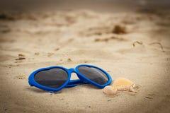 Błękitni okulary przeciwsłoneczni kształtowali serce z skorupami na piasku przy plażą obrazy royalty free