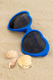 Błękitni okulary przeciwsłoneczni w kształcie serce i skorupy na piasku przy plażą Obrazy Stock