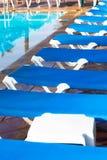 Błękitni pokładów krzesła układali wokoło basenu przed lub po en Obrazy Stock