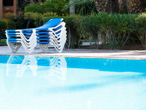 Błękitni pokładów krzesła układali wokoło basenu przed lub po en Zdjęcie Stock