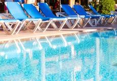 Błękitni pokładów krzesła układali wokoło basenu przed lub po en Obrazy Royalty Free
