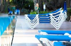 Błękitni pokładów krzesła układali wokoło basenu przed lub po en Obraz Stock