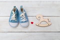 Błękitni sneakers dla zabawkarskiego drewnianego konia na drewnianym backg i dzieciaka Zdjęcie Stock