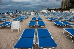 Błękitni sunbeds w starannych rzędach w południe plaży, Miami; burzowy dzień, siwieje chmury obraz stock
